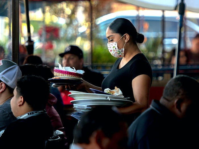 A worker serving people at a restaurant